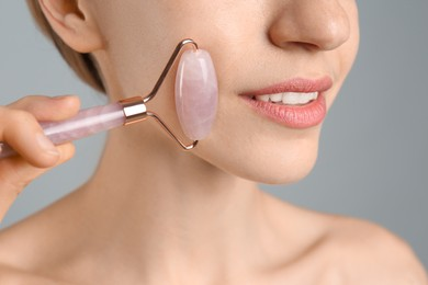 Young woman using natural rose quartz face roller on light grey background, closeup