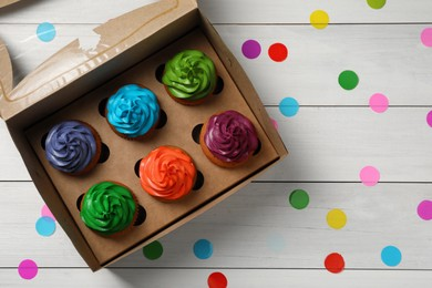 Box with different cupcakes and confetti on white wooden table, flat lay. Space for text