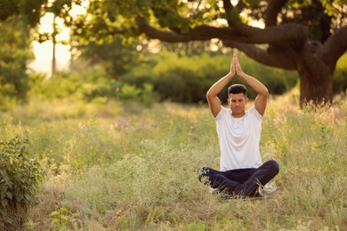 Man meditating on green grass in park, space for text