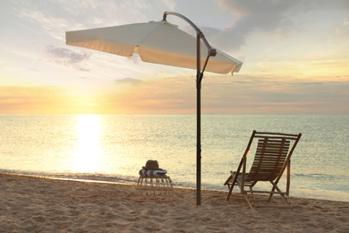 Wooden deck chair, outdoor umbrella and wicker table on sandy beach at sunset. Summer vacation
