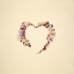Beautiful heart shaped floral composition on beige background, flat lay