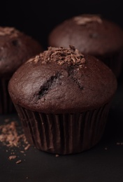 Delicious cupcakes with chocolate crumbles on black table, closeup