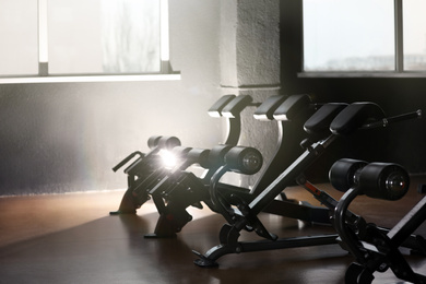 Row of back extension machines in modern gym