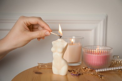 Woman lighting female body shaped candle on wooden table, closeup. Stylish decor
