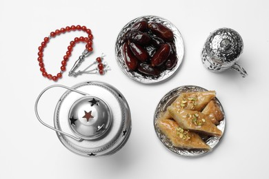 Composition with Arabic lantern and snacks on white background, top view