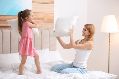 Mother playing with her child in bedroom at home