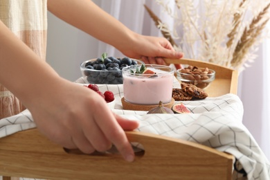 Woman holding wooden tray with delicious breakfast and fig smoothie, closeup