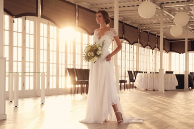 Gorgeous bride in beautiful wedding dress with bouquet in restaurant