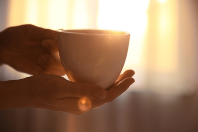 Woman holding cup of drink on blurred background, closeup. Lazy morning