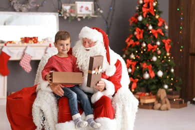 Little boy with gift box sitting on authentic Santa Claus' lap indoors