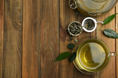Flat lay composition with cup of green tea on wooden table. Space for text