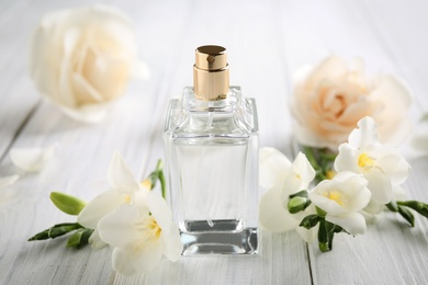 Bottle of perfume and beautiful flowers on white wooden table