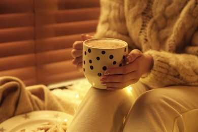 Woman with cup of hot drink at home, closeup