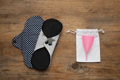 Reusable cloth pads and menstrual cup on wooden table, flat lay