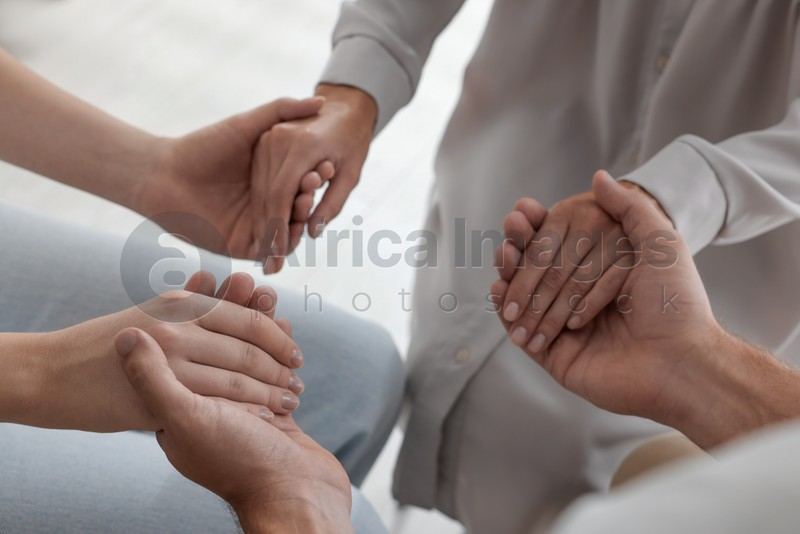 Group of religious people holding hands and praying together indoors, closeup