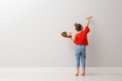 Little girl painting on light grey wall indoors, back view. Space for text