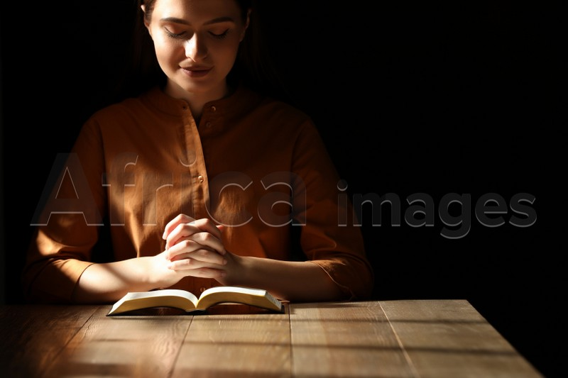 Religious young woman praying over Bible at wooden table indoors