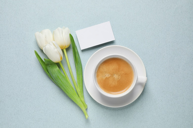White tulips, coffee and blank card on light blue background, flat lay. Good morning