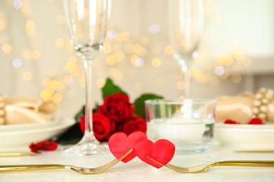 Golden forks with red hearts on white table. Romantic dinner