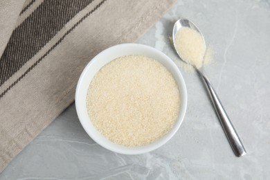 Gelatin powder in bowl and spoon on light grey marble table, flat lay