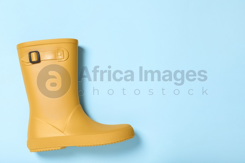 Yellow rubber boot on light blue background, top view. Space for text