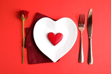 Elegant table setting for romantic dinner on red background, flat lay. Valentine's day celebration