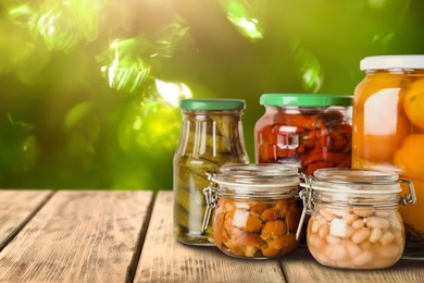 Jars of different pickled foods on wooden table against blurred background, space for text