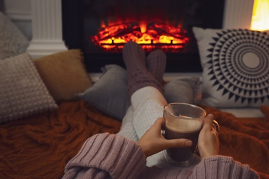 Woman with cup of coffee sitting near burning fireplace, closeup