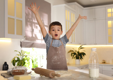 Emotional little boy at table with cooking ingredients in kitchen