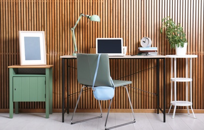 Stylish workplace interior with laptop on table near wooden wall. Space for text