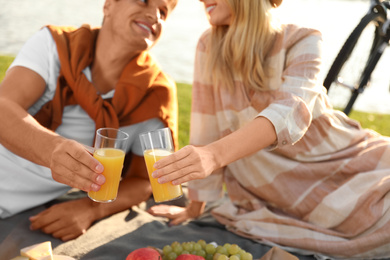 Young couple having picnic outdoors, focus on hands with glasses of juice