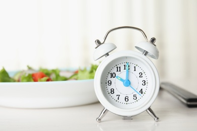 Alarm clock and plate with salad on white table. Meal timing concept