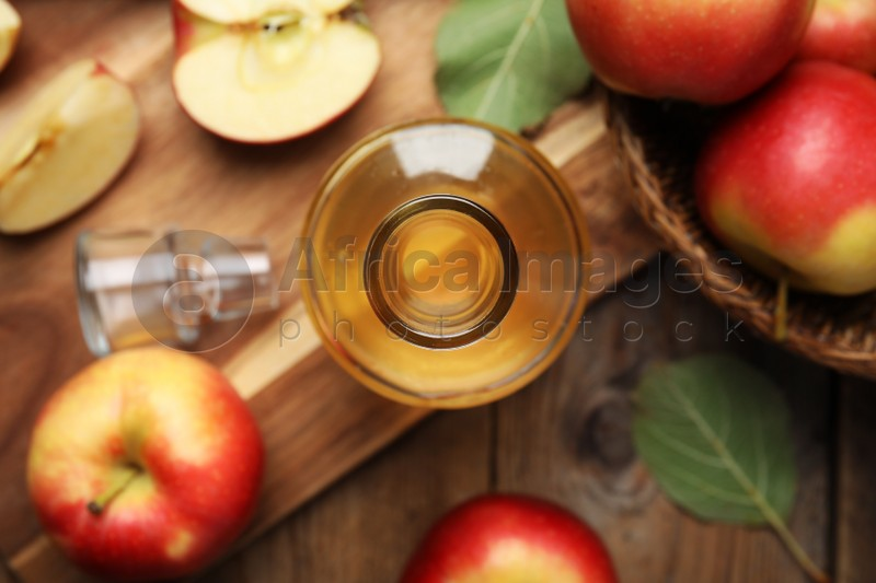 Natural apple vinegar and fresh fruits on wooden table, flat lay