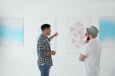 Men discussing artworks at exhibition in art gallery