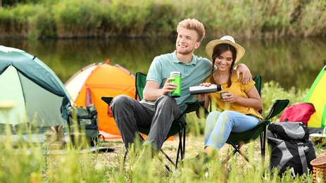 Young couple with hot drinks resting outdoors. Camping vacation