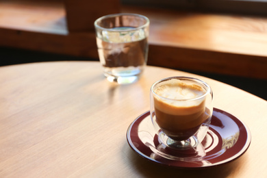 Aromatic coffee on wooden table in cafe. Space for text