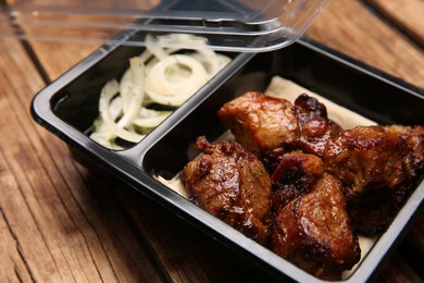 Plastic container of tasty shish kebab on wooden table, closeup. Food delivery service