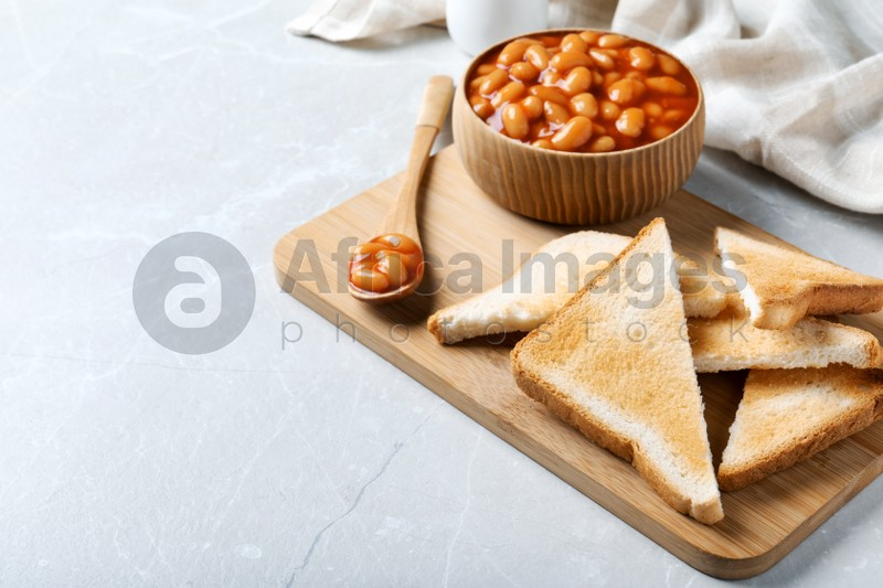 Toasts and delicious canned beans on white table, space for text