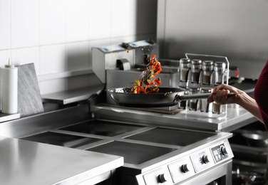 Woman cooking tasty food on stove in restaurant  kitchen, closeup