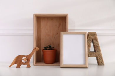 Empty photo frame, cute toy dinosaur, wooden letter and crate with houseplant near wall, space for text. Baby room interior element