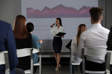 Female business trainer giving lecture in conference room with projection screen