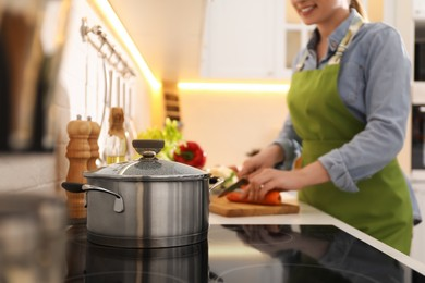 Homemade bouillon recipe. Woman cutting carrot in kitchen, focus on pot