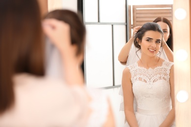 Professional hairdresser working with young bride in salon