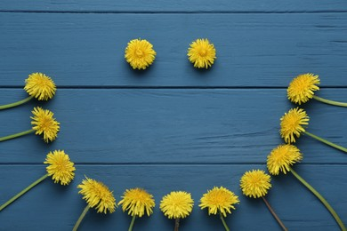 Funny face made of beautiful yellow dandelions on blue wooden table, flat lay
