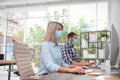 Office employees in respiratory masks at workplace
