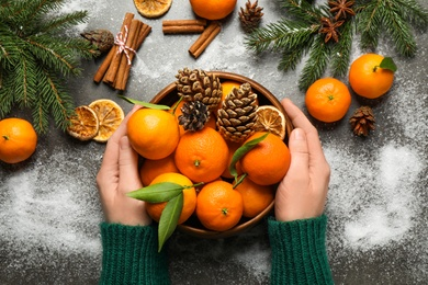 Woman with fresh tangerines at table, top view. Christmas atmosphere