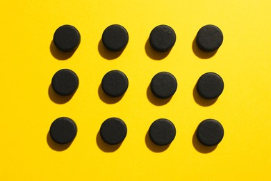 Activated charcoal pills on yellow background, flat lay. Potent sorbent