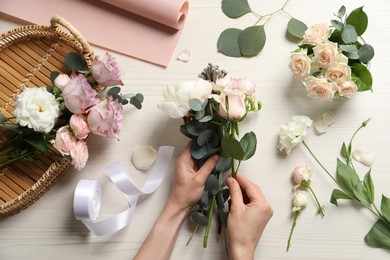 Florist creating beautiful bouquet at white table, top view