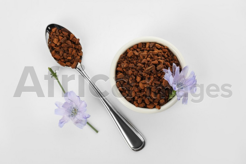 Chicory granules and flowers on white background, top view