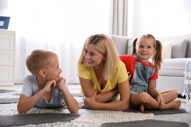 Happy mother with her children on floor at home